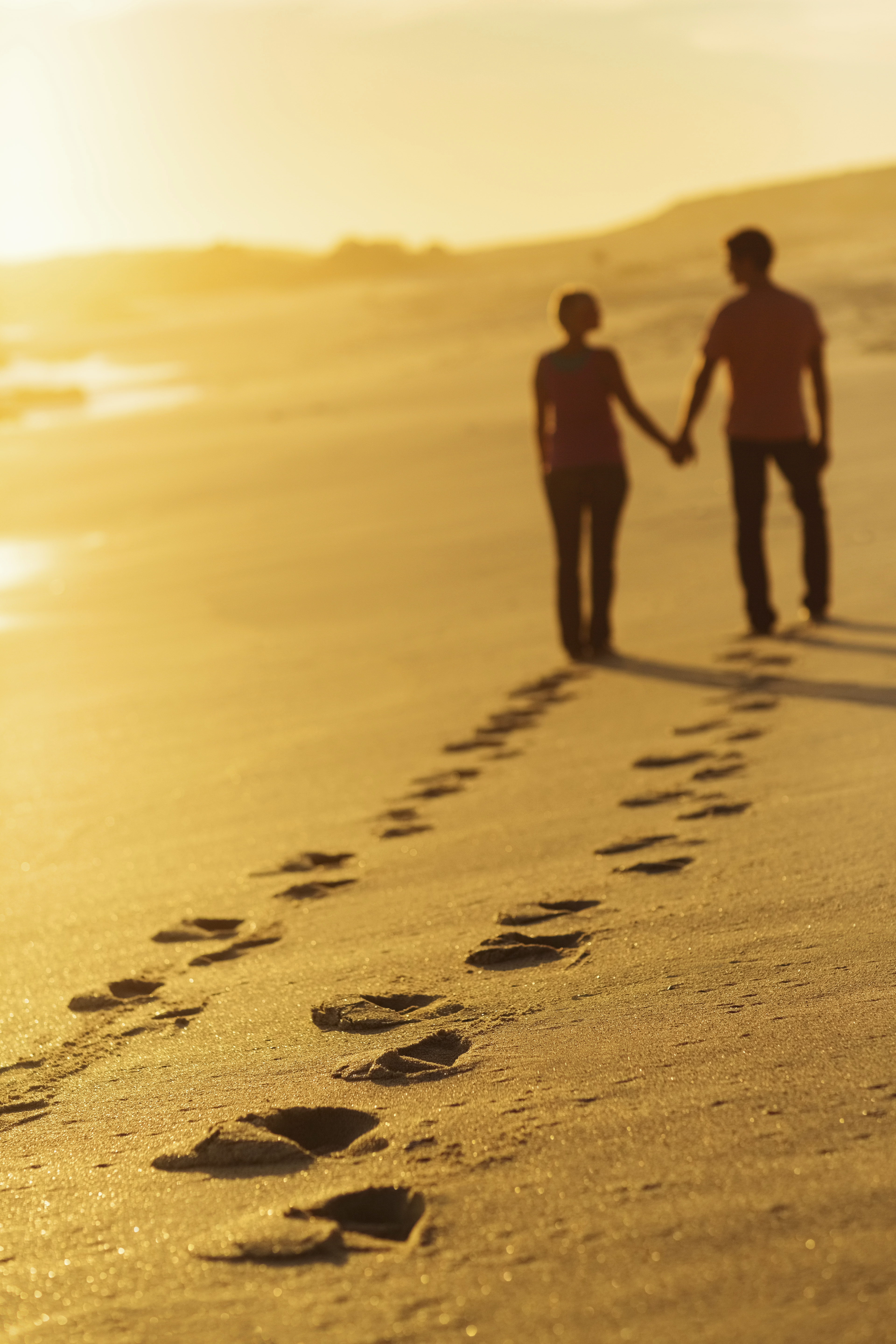 Footprints Track With Couple Walking On Beach At Sunset